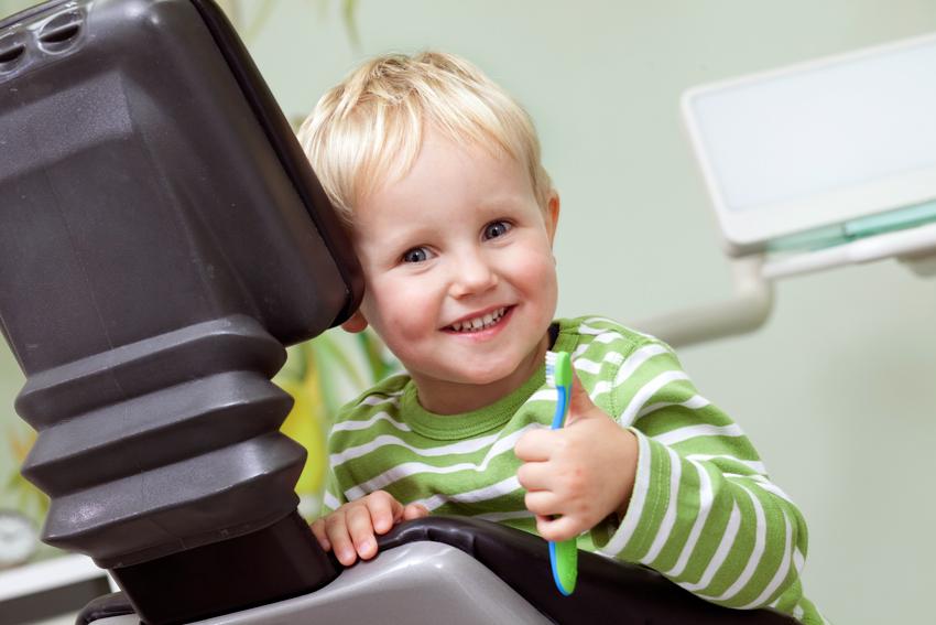 Fröhliches Kind auf Zahnarztstuhl